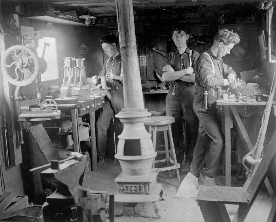 Left to right are Fritz, Jacob and Ernest Warther working in their shop in 1907. Ernest (Nicknamed Mooney) is carving on wood with an early pocketknife he made.