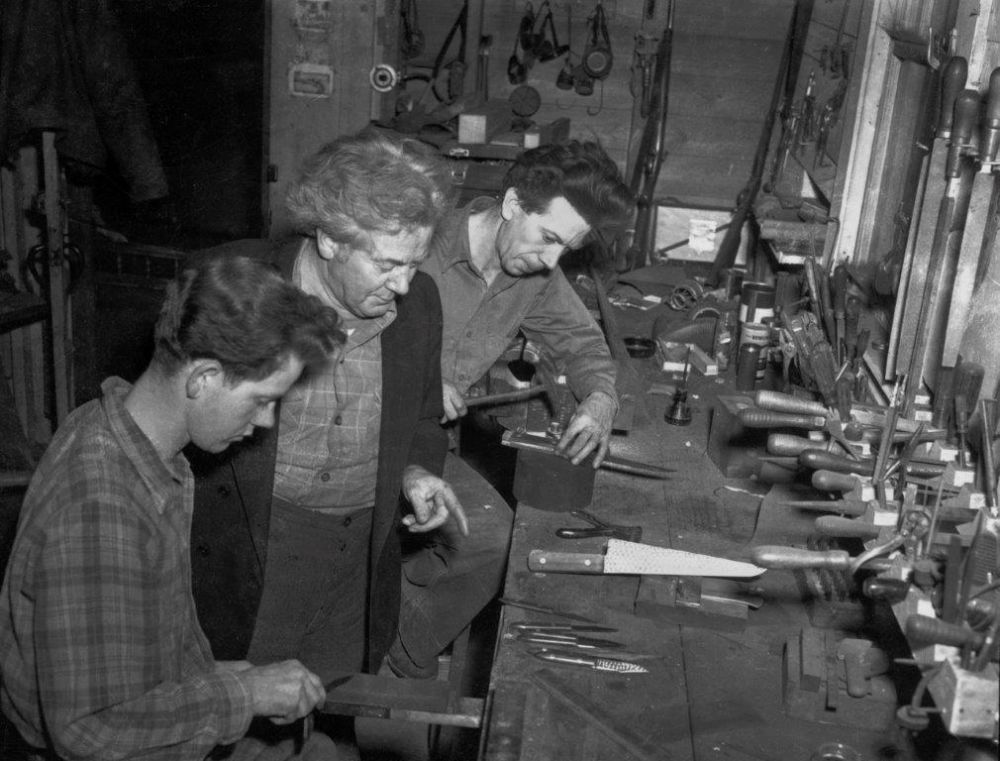 Mooney (Center) with sons Tom and Dave (Front left) in the knife shop circa 1950.